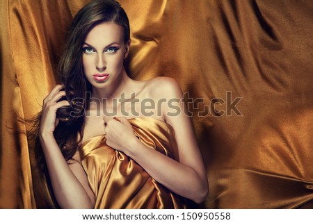 Attractive brunette woman in golden fabric