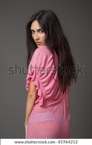 Attractive brunette woman in pink dress