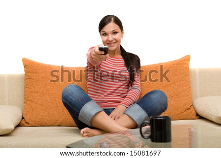 attractive brunette woman on sofa with remote control