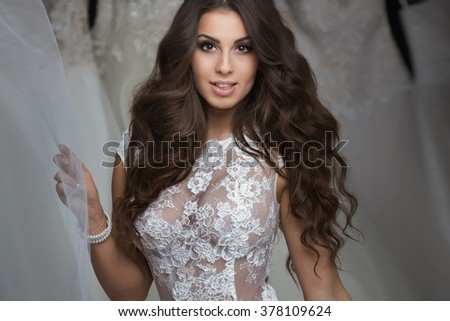 Attractive brunette woman posing in white bridal dress. Studio shot. Beautiful girl. - stock photo