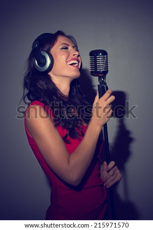 Attractive brunette woman recording a song in music studio. - stock photo