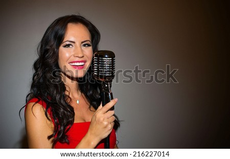 Attractive brunette woman singing into vintage microphone. - stock photo
