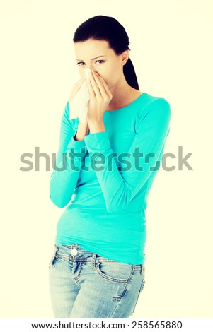 Attractive brunette woman sneezing in a tissue. - stock photo