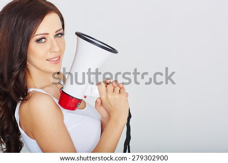 Attractive brunette woman with a megaphone in studio - stock photo