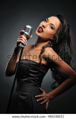 Attractive brunette woman with a retro microphone - stock photo