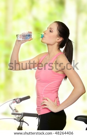 Attractive brunette woman with bike in forest drinking water - stock photo