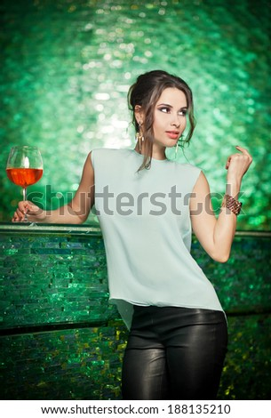 Attractive brunette woman with long hair in elegant light green blouse and black leather pants standing on bar stool with a glass. Gorgeous brunette model posing in a modern green textured scenery - stock photo