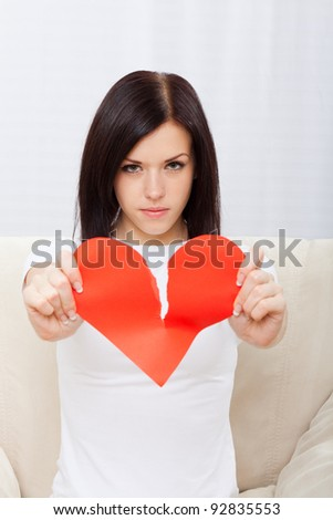 Attractive brunette young girl holding broken paper red valentine heart, woman sitting on couch at home, concept of unhappy love valentine's day - stock photo