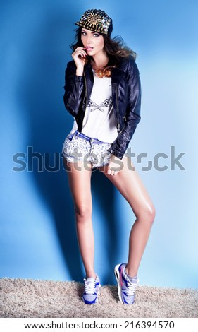 Attractive brunette young woman posing in fashionable clothes, looking at camera. Girl with long slim legs and curly hair. Studio shot. - stock photo