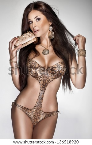 Attractive brunette young woman with long healthy hair posing in fashionable swimsuit. A lot of gold jewelry. Perfect body. - stock photo