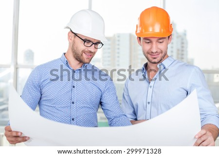 Attractive builders are looking at sketches of new project. The engineer is explaining to foreman the main concepts with aspirations. They are smiling with joy - stock photo