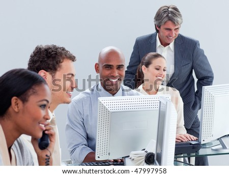 Attractive business colleagues working at a computer in the office - stock photo