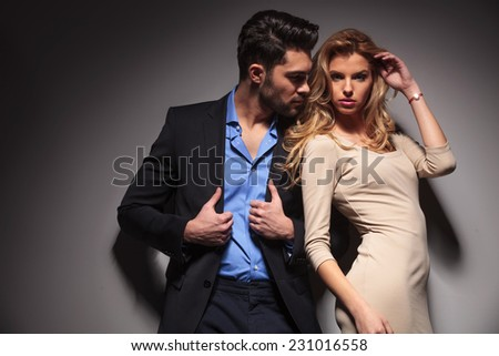 Attractive business man fixing his jacket while looking at his lover. The beautiful blonde woman is fixing her hair while looking at the camera. - stock photo