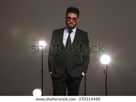 attractive business man in black suit posing with hands in pockets in studio with spotlights - stock photo