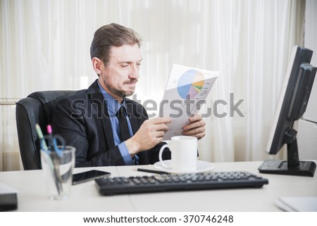 attractive business man is sitting on his desktop and smiles - stock photo