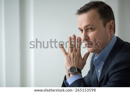 Attractive business man sitting pensively looking out the window propped his chin. - stock photo
