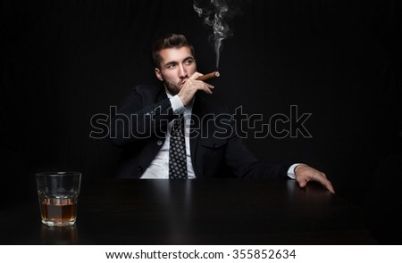 Attractive business man with a cigar and a whiskey - stock photo