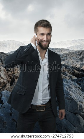 Attractive business man with a mobile phone alone in the mountains