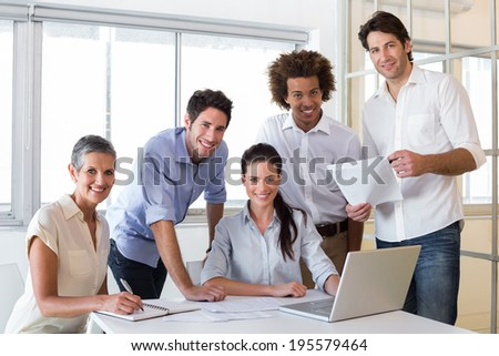 Attractive business people smiling at the camera whilst working - stock photo