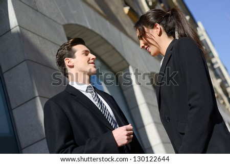 Attractive business people talking outside of company building. Couple working. - stock photo