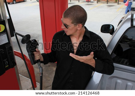 Attractive Business Professional Upset and Confused at Gas Prices Holding Gas Pump Upset