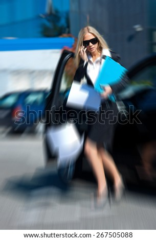 attractive business woman dropping papers near to her car in parking lot, zoomed for dramatic effect - stock photo