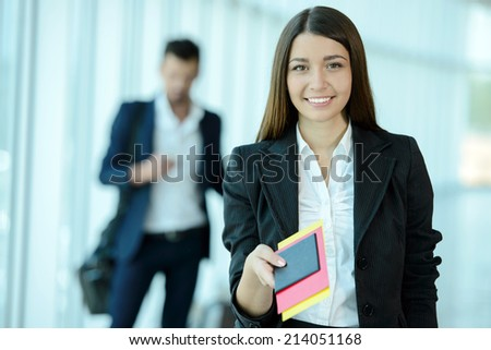 Attractive business woman handing over air ticket at airport check in counter - stock photo