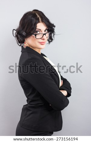 Attractive business woman in a black jacket.Beautiful girl with glasses in black frame.Stylish brunette on a gray background - stock photo