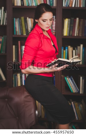 attractive business woman in office attire standing against the background of bookshelves in a library or office and reading a book. Education concept. - stock photo