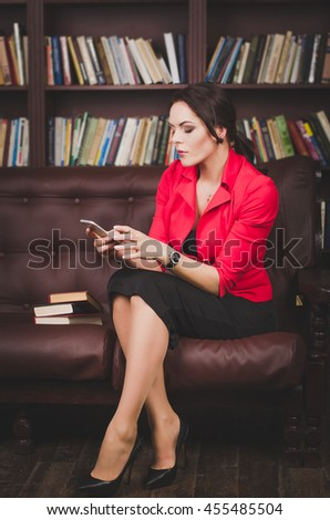 attractive business woman in office clothes sitting on a leather couch korchnevom and looking at the phone, behind her are large bookshelves. business concept - stock photo