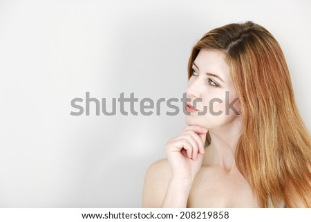 Attractive business woman leaning against an office wall expressing concern and thinking.