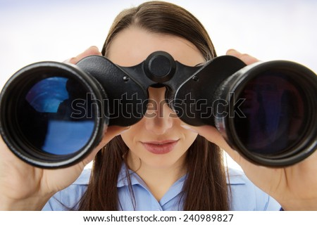attractive business woman looking through binoculars