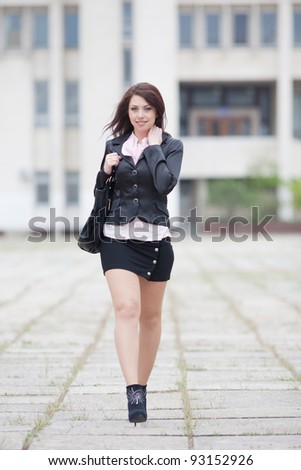 Attractive business woman on background of white wall. Cute business woman walking outside on a grey day