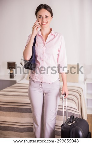 Attractive business woman talking by phone, looking at camera and holding suitcase while standing at the hotel room. - stock photo