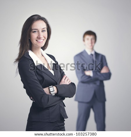 Attractive business woman with her arms crossed.Businessman on background - stock photo