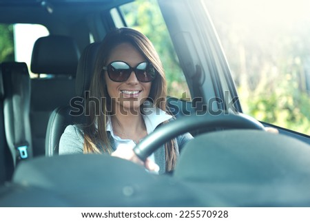 Attractive business woman with sunglasses smiling and driving her car. - stock photo