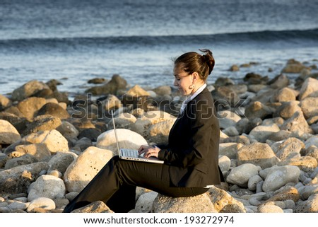 attractive business woman working on a laptop sitting on some rocks at the beach looking up to sky thinking about freedom - stock photo