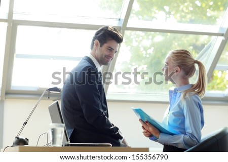 Attractive businessman and businesswoman flirting with each other as they work