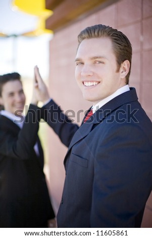 Attractive businessman and businesswoman giving high-five