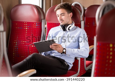Attractive businessman and entertainment during long ride by train - stock photo