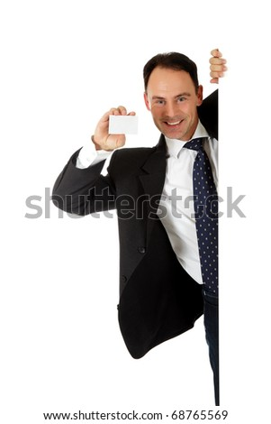 Attractive businessman behind wall showing a blank, white business card. Copy paste. Studio shot. White background. - stock photo