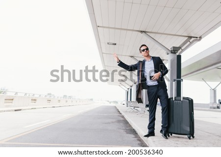 Attractive businessman calling a taxi at the airport - stock photo
