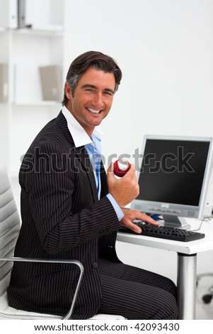 Attractive businessman eating an apple in an office