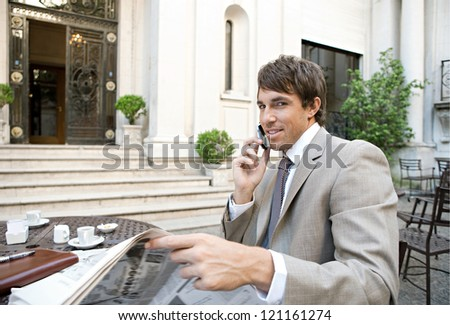 Attractive businessman having a cell phone conversation while reading the newspaper in a coffee shop terrace with classic office buildings in the background. - stock photo