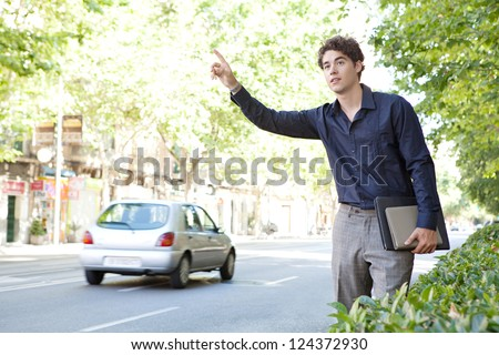Attractive businessman hitching a taxi in a tree aligned street in the city, holding paperwork and folders. - stock photo