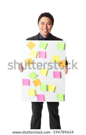 Attractive businessman holding a board with post it notes on it. White background.