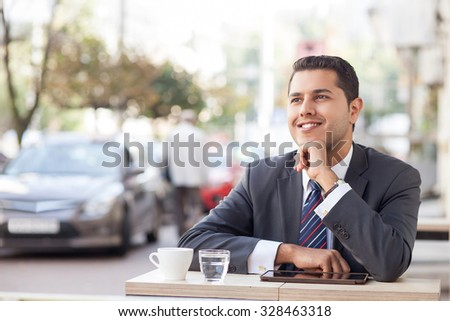 Attractive businessman is sitting and relaxing in cafe outdoors. He is dreaming and smiling. The worker is drinking coffee. There are a tablet and cup of water on table - stock photo