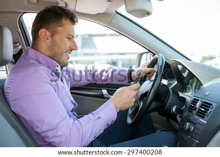 Attractive businessman is sitting at steering wheel of his car and smiling. He is holding mobile phone and looking at it with concentration. He wants to call his colleague - stock photo