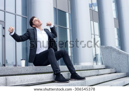 Attractive businessman is sitting on steps near his office. He is stretching himself sleepily. His eyes are closed. The guy is trying to wake up with the cup of coffee - stock photo