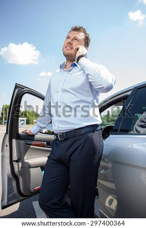 Attractive businessman is talking on the mobile phone. He is standing near his car and leaning his hand on door. He is smiling and looking aside - stock photo
